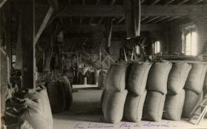 Un exemple d'aménagement intérieur de magasin à grain. Au premier plan, les sacs sont empilés. A l'arrière plan, un équipement mécanique rudimentaire certainement dédié à l'épuration de la matière.
